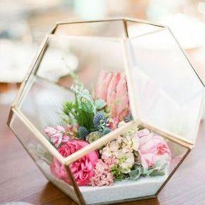 Centre de table de mariage fleuri avec une serre