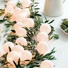 Centre de table mariage avec guirlande lumineuse et branches d'olivier