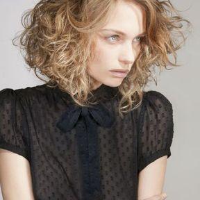 Jeune femme coupe de cheveux sur les cheveux bouclГ©s