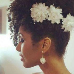 Chignon banane de mariage avec fleurs pour cheveux frisés