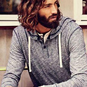 Beau gosse à barbe aux cheveux ondulés