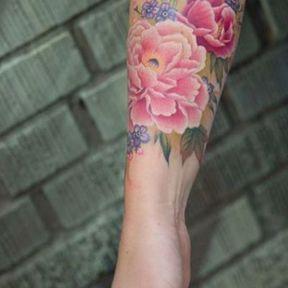 Tatouage coloré tout du long de l'avant-bras