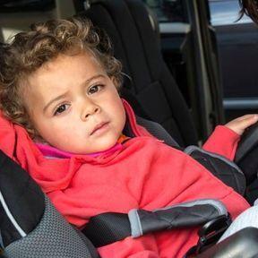 Epaules de l'enfant en dehors du harnais (siège-auto)